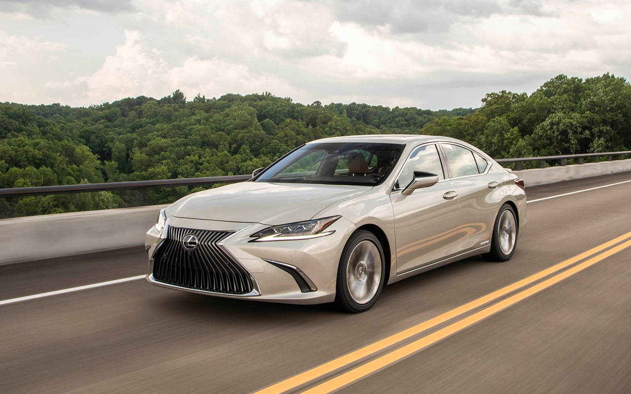 2021 Lexus ES 300h in moonbeam beige driving on a highway with trees in the background